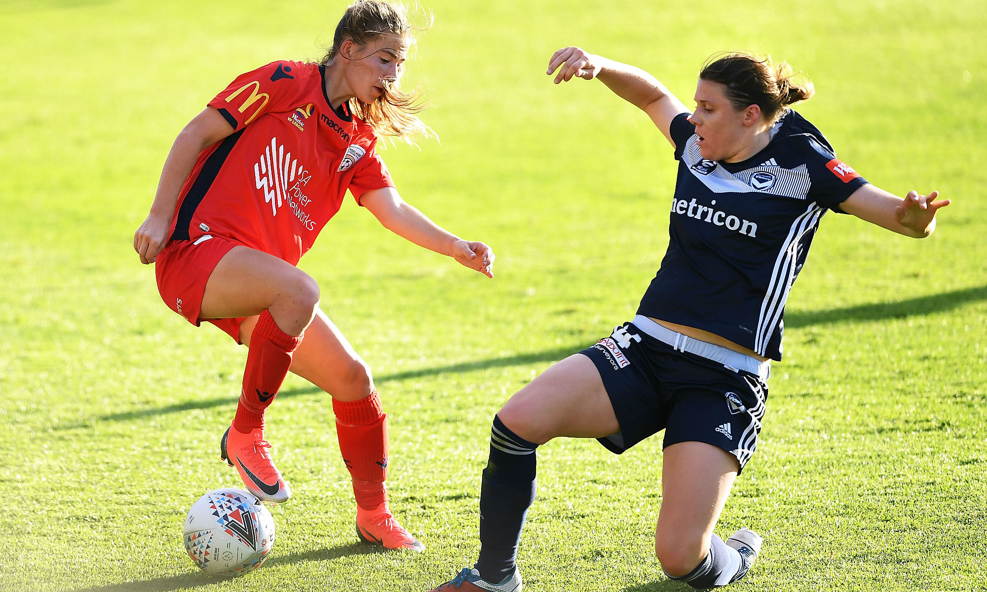 Adelaide's Emily Hodgson takes Melbourne Victory's Melina Ayres in the Westfield W-League's version of the Original Derby.