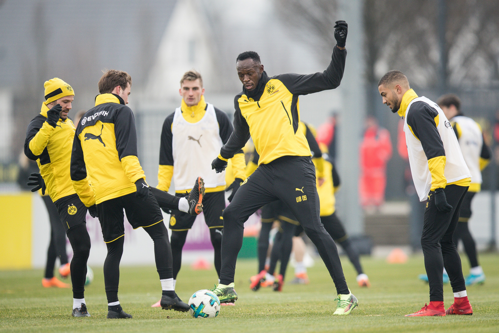 Bolt tackles German midfielder Mario Gotze while training with Borussia Dortmund