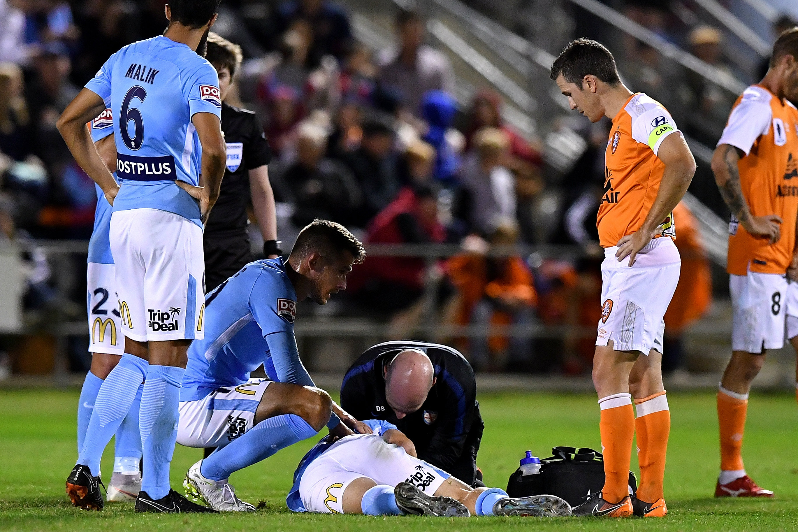 Luke Brattan receives treatment from City medical staff.