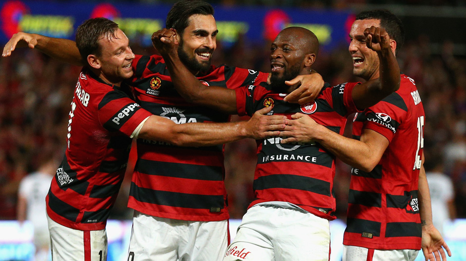 Wanderers players celebrate one of Romeo Castelen's three goals against the Roar.
