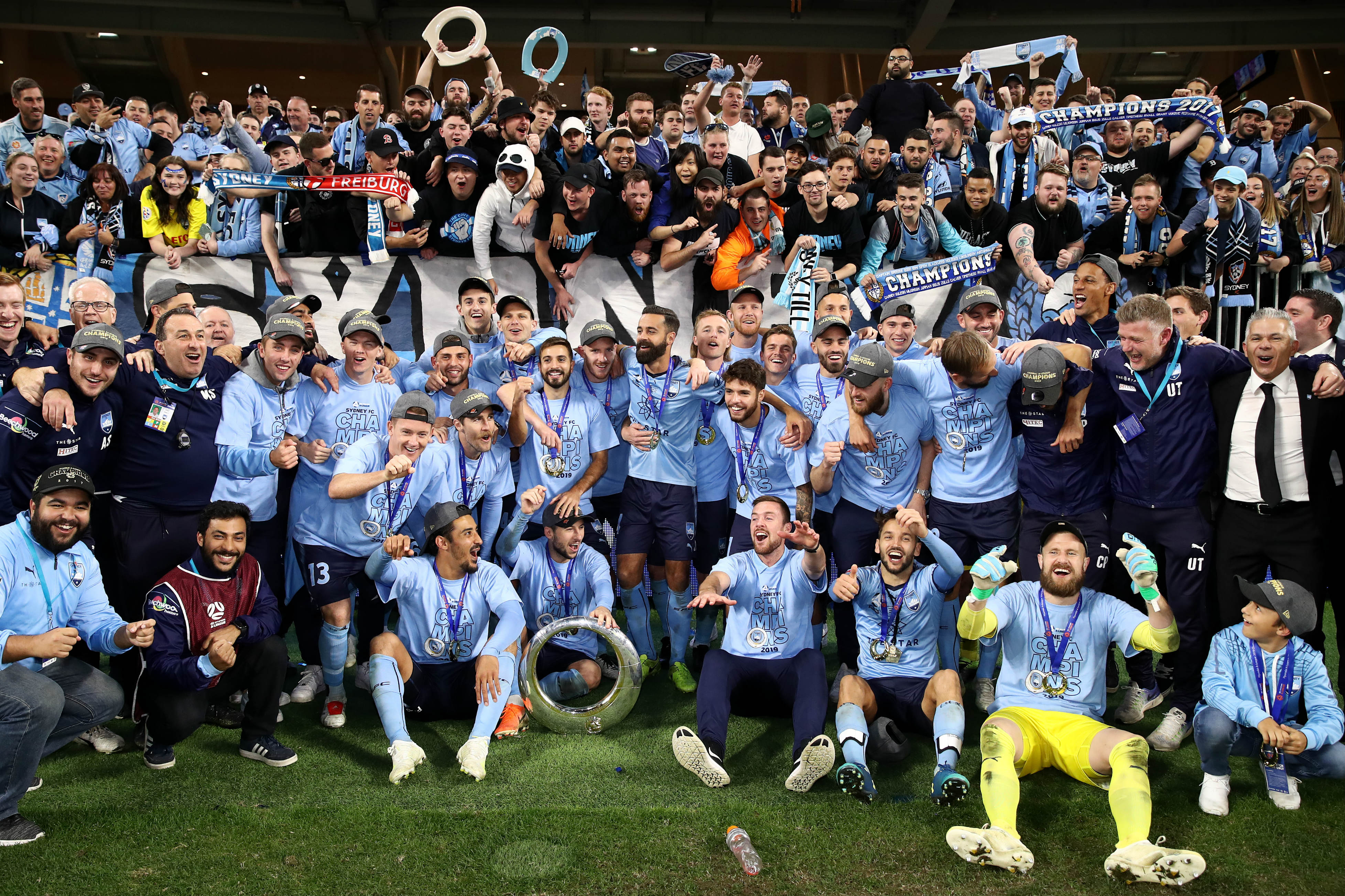 Sydney FC players pose for a snap in front of the travelling fans