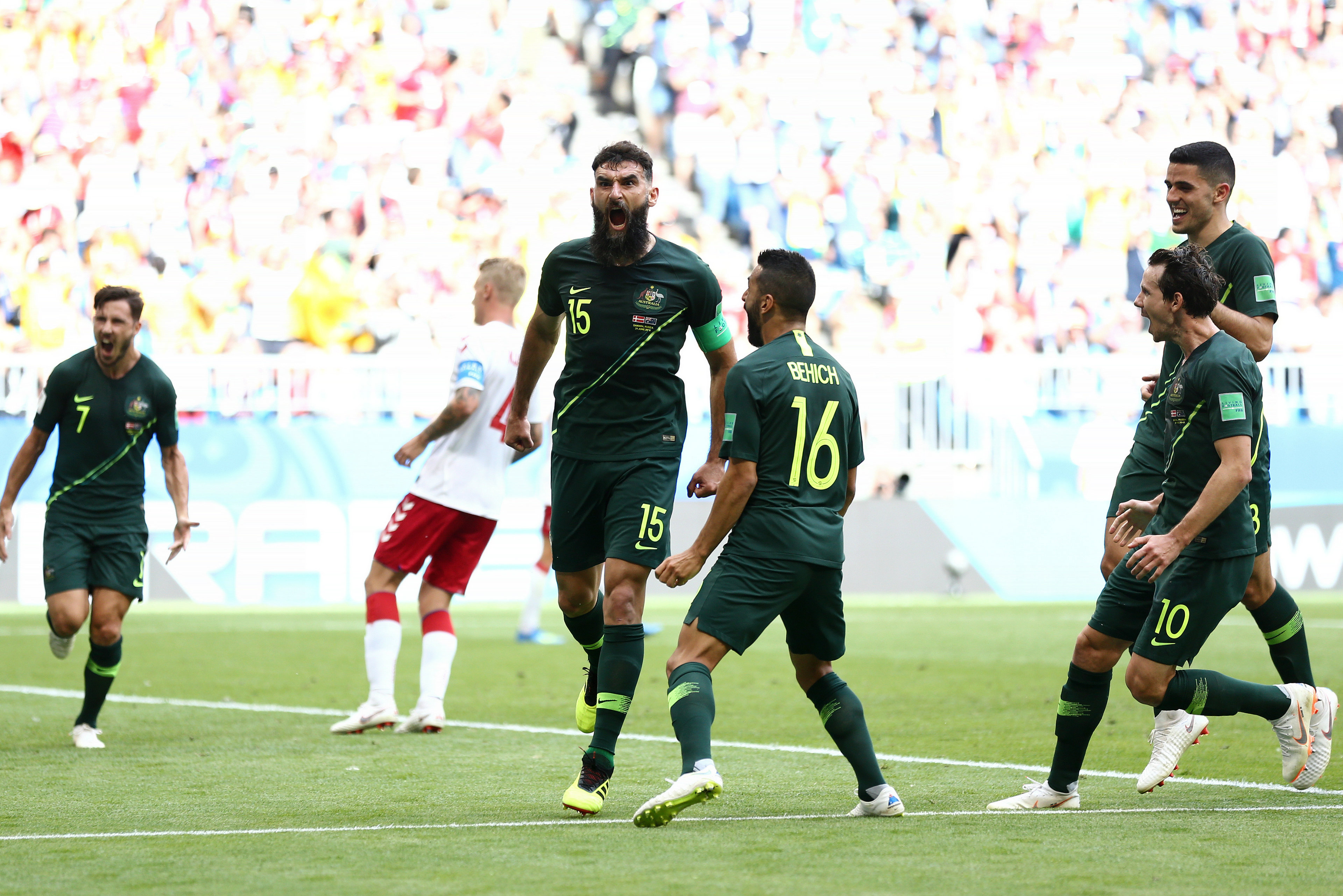 The Socceroos get around skipper Mile Jedinak after his penalty.