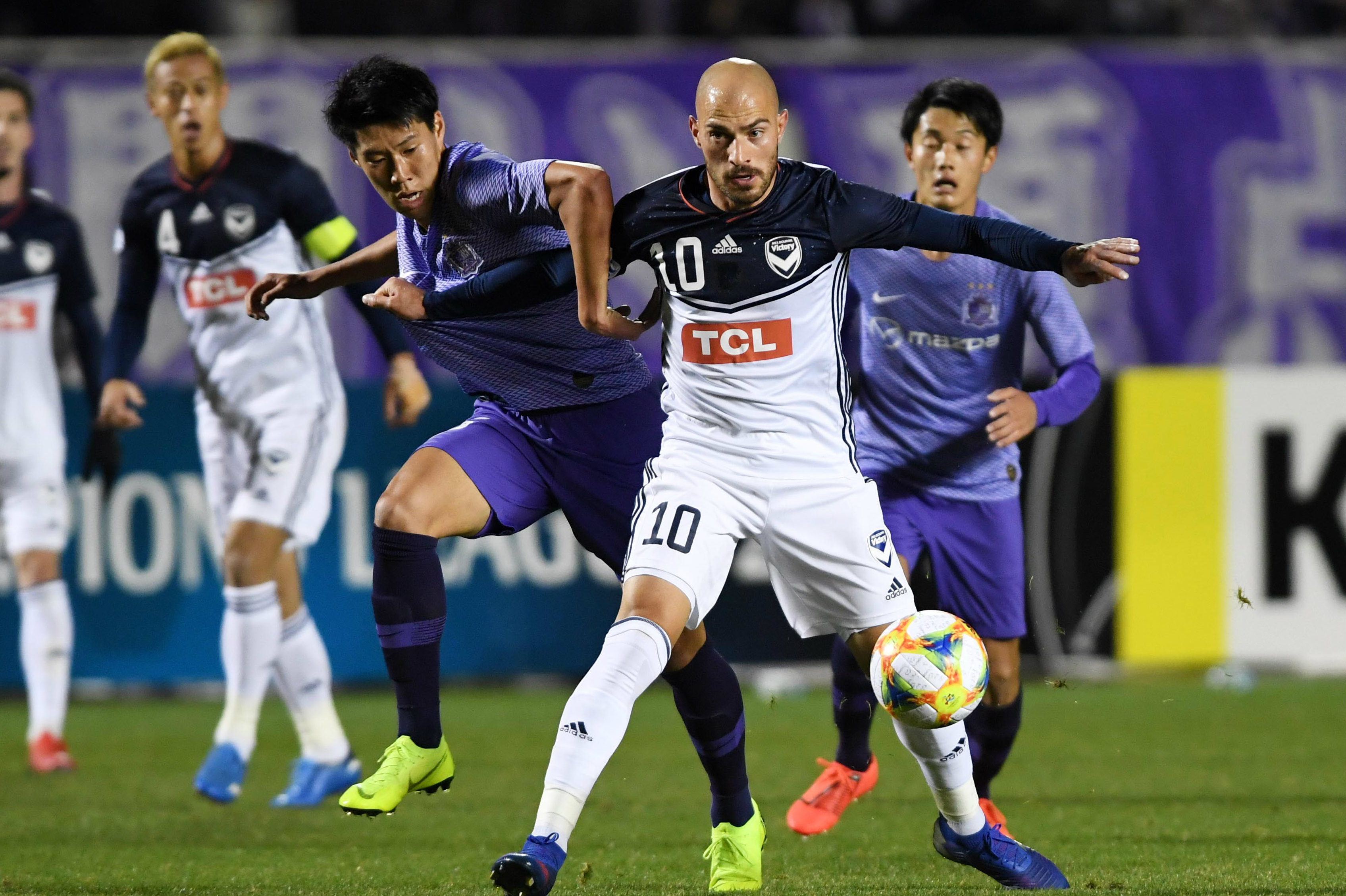 Victory's James Troisi holds off an opponent in the loss to Sanfrecce Hiroshima