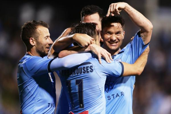 Sydney FC players celebrate with Barbarouses after his goal