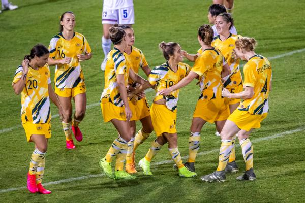 Katrina Gorry is swamped by teammates after scoring the Westfield Matildas' seventh