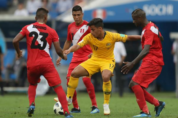 Three Peruvian players surround Daniel Arzani in the game in Sochi.