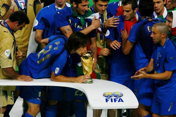 Andrea Pirlo kisses the FIFA World Cup trophy, standing alongside former Sydney FC player Alessandro Del Piero